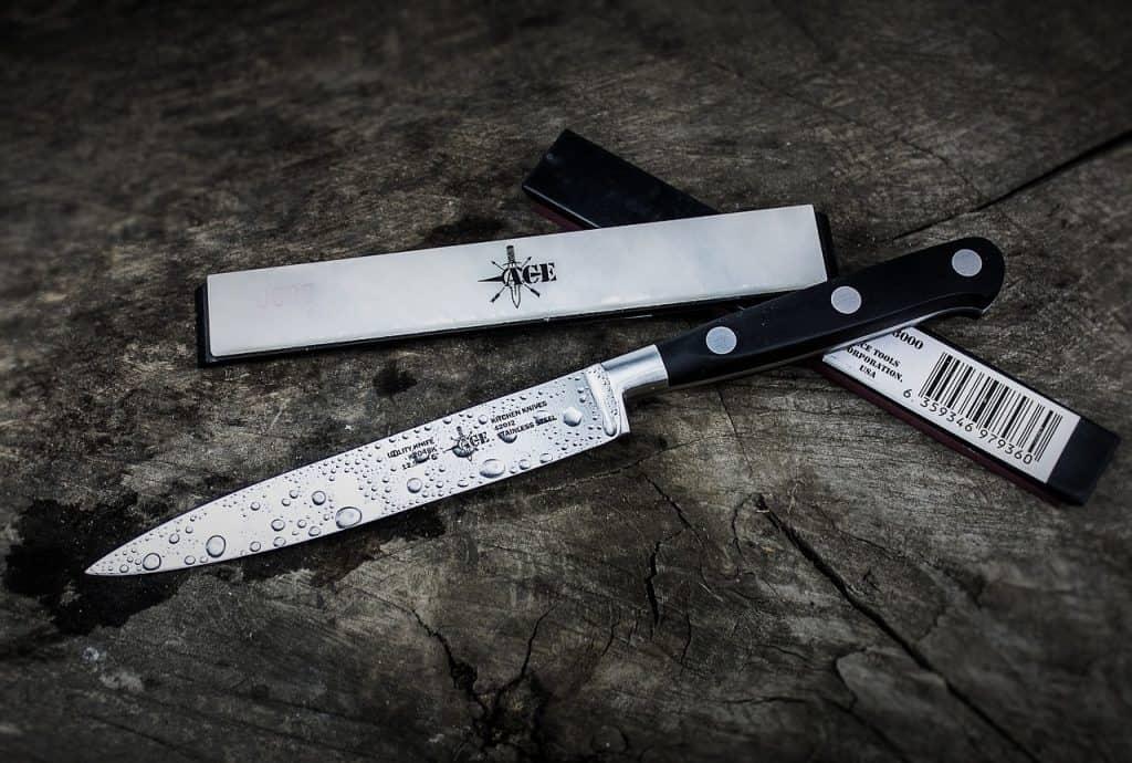 Imagem de faca de aço damasco sobre mesa com gotas de água.