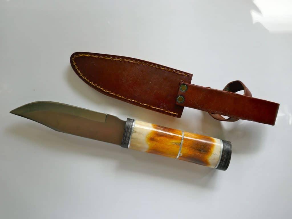 Imagem de faca de caça e bainha.