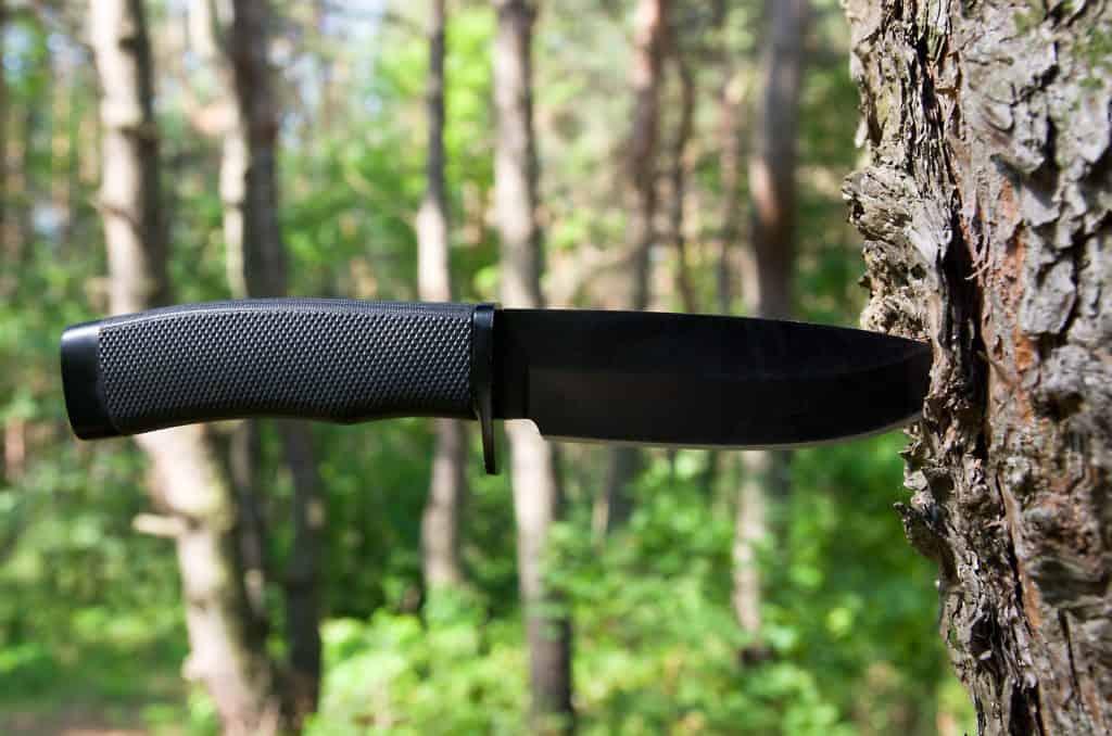 Uma faca de caça fincada em um tronco de árvore.