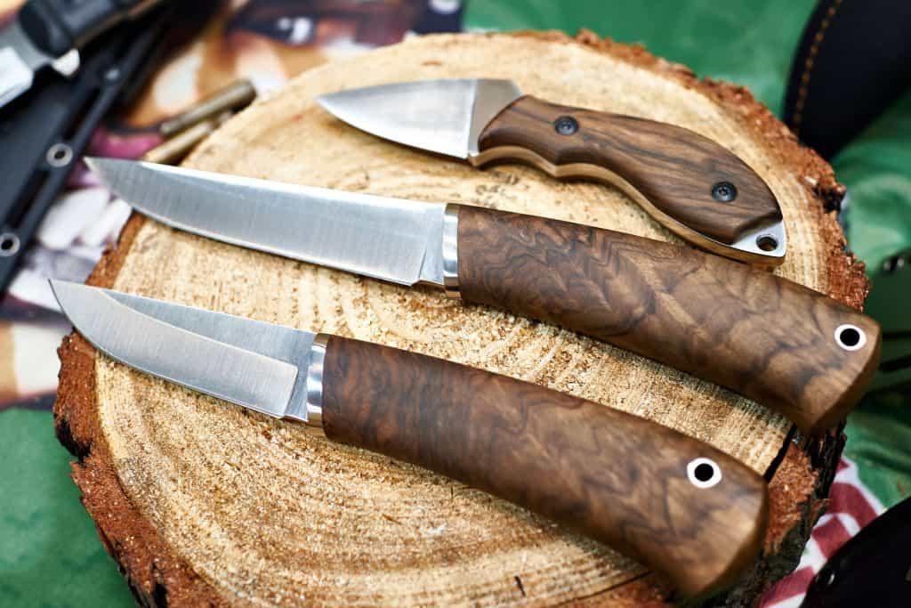 Três facas de caça lado a lado sobre um tronco de madeira.
