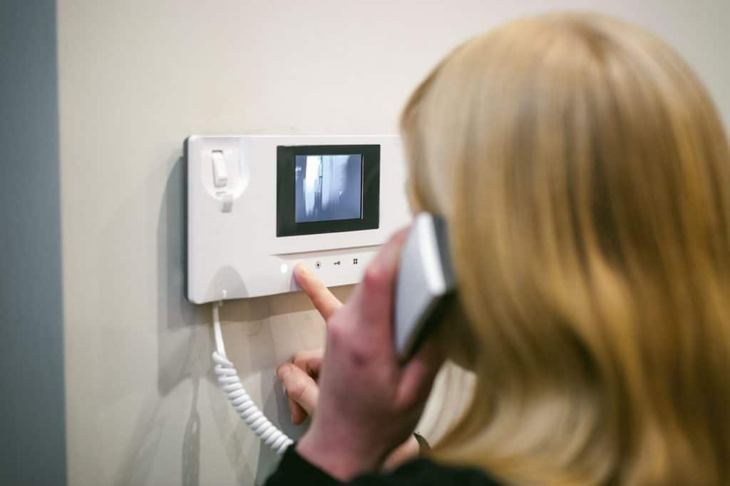 Imagem de uma mulher usando um vídeo-porteiro.