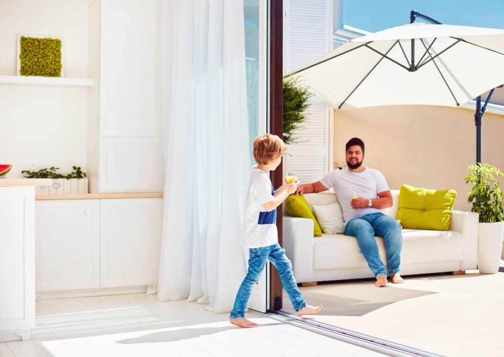 Imagem de um homem sentado embaixo de um ombrelone e uma criança passando na sua frente em uma linda casa.
