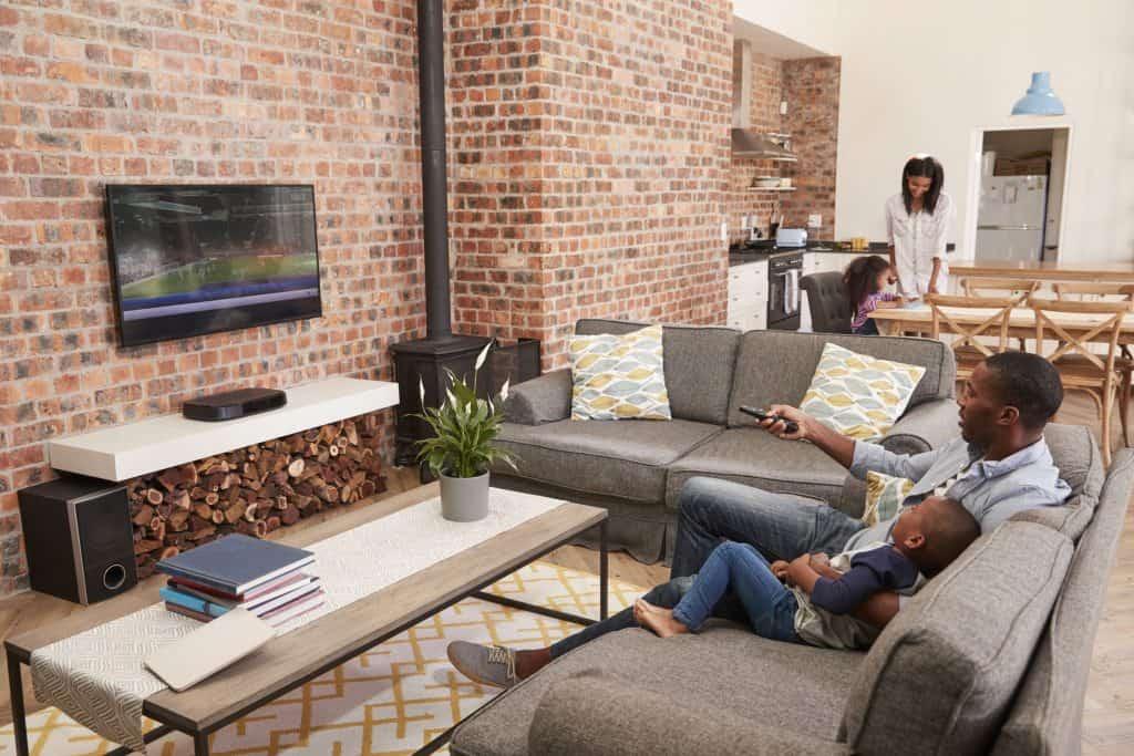 Imagem mostra mulher ambiente integrado, pai e filho estão no sofá vendo tv e mãe filha estão na mesa da cozinha.