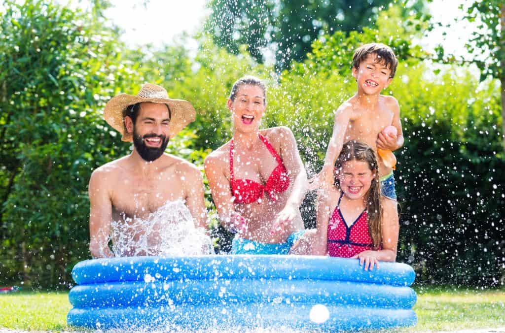 Imagem de família tomando banho em piscina inflável.