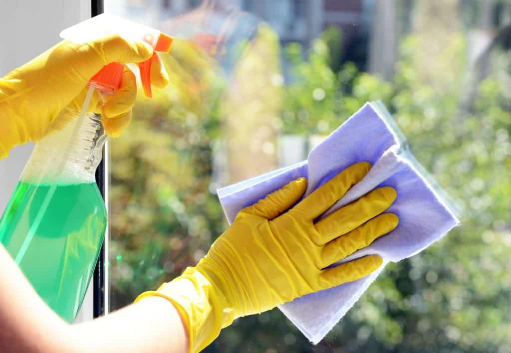 Pessoa usando luvas amarelas limpando vidro com borrifador e pano.