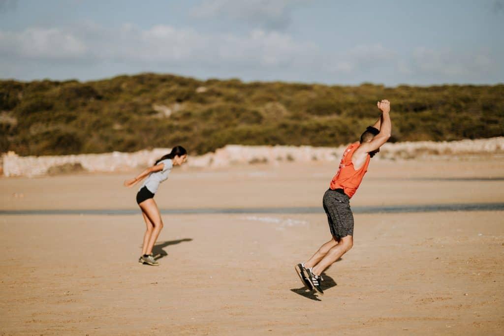 Imagem mostra um homem e uma mulher fazendo exercícios na praia.