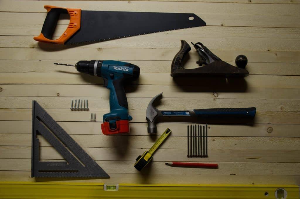 Imagem mostra um esquadro em meio à uma composição de ferramentas básicas, como martela, furadeira, trena, etc, sobre uma superfície de madeira.
