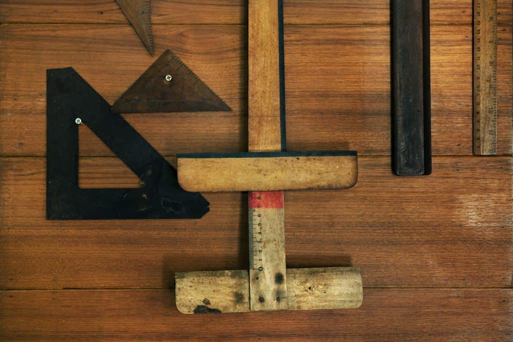 Uma régua T de madeira sobre superfície de madeira com outras ferramentas ao redor.