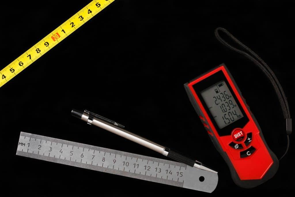 Trena a laser sob superfície preta ao lado de régua, caneta e trena comum.