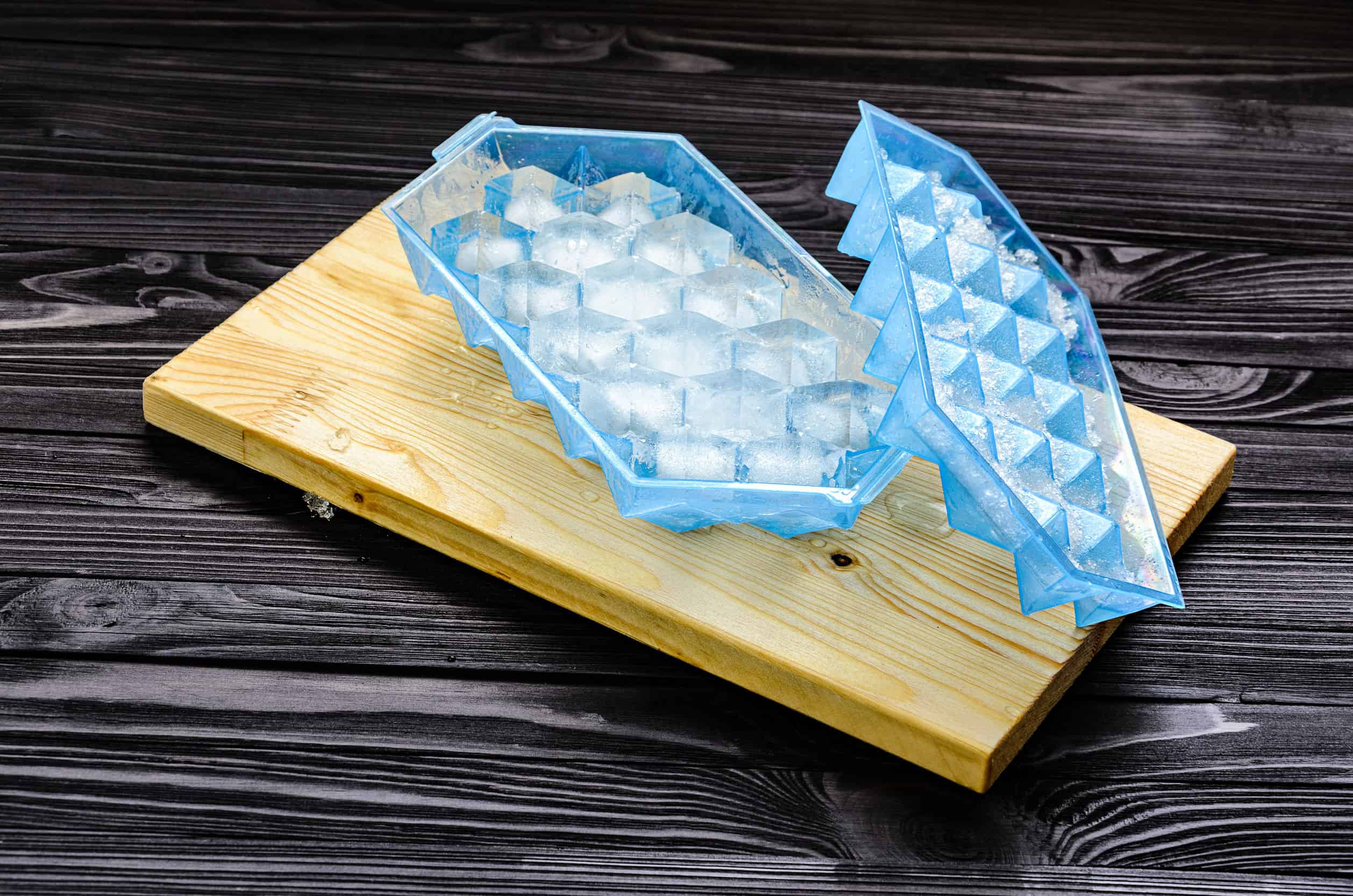Na foto estão duas formas de gelo azuis em cima de uma tábua.