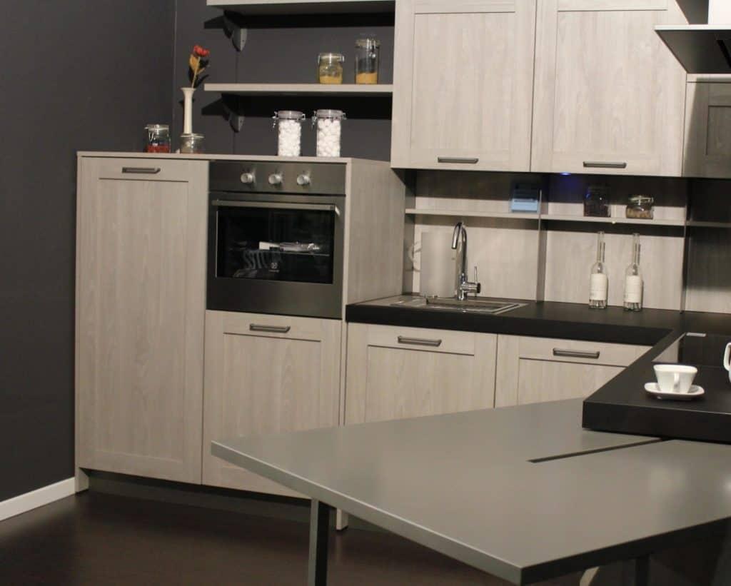 Imagem mostra um forno embutido em um móvel em uma cozinha que possui diversos armários e uma mesa.