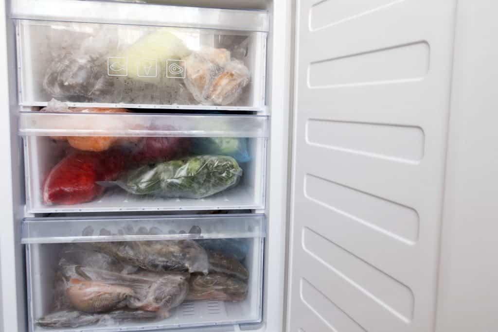 Imagem de freezer aberto com itens dentro.
