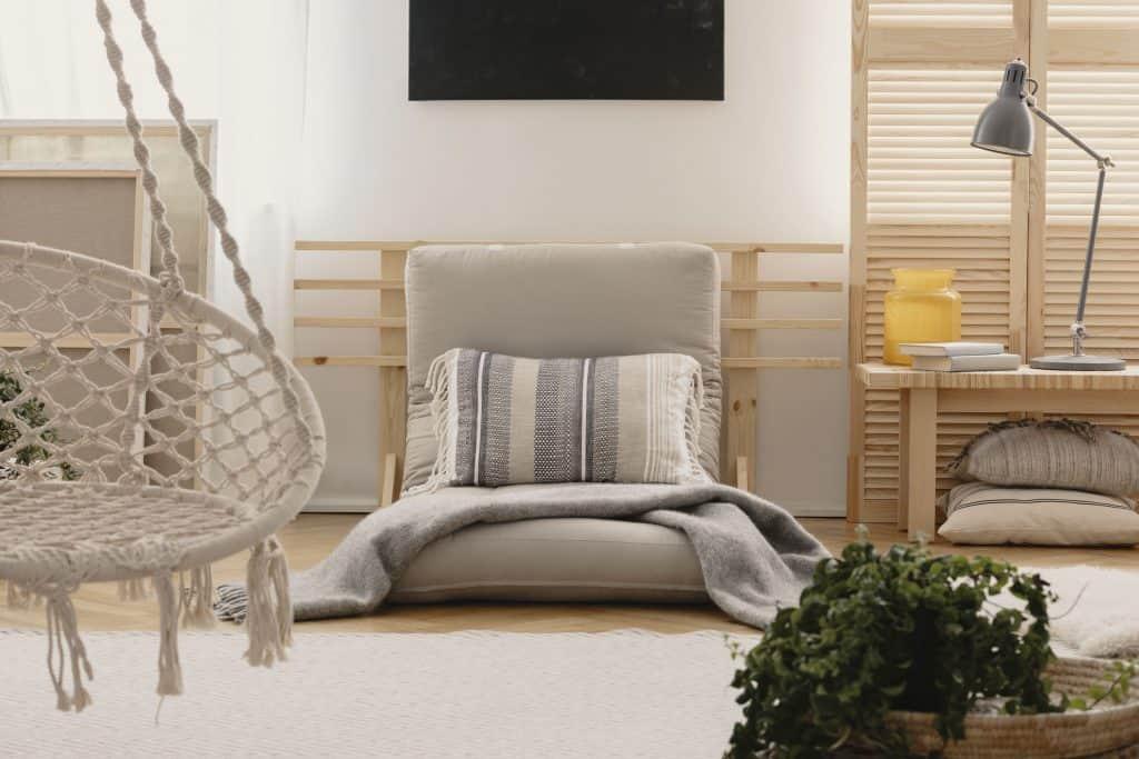 Imagem de um quarto com um futon cinza claro.