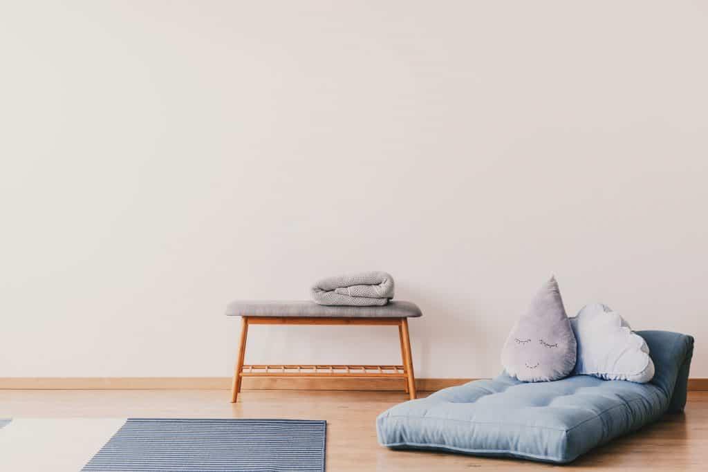 Imagem de um futon azul com almofadas em cima ao lado de um tapete.