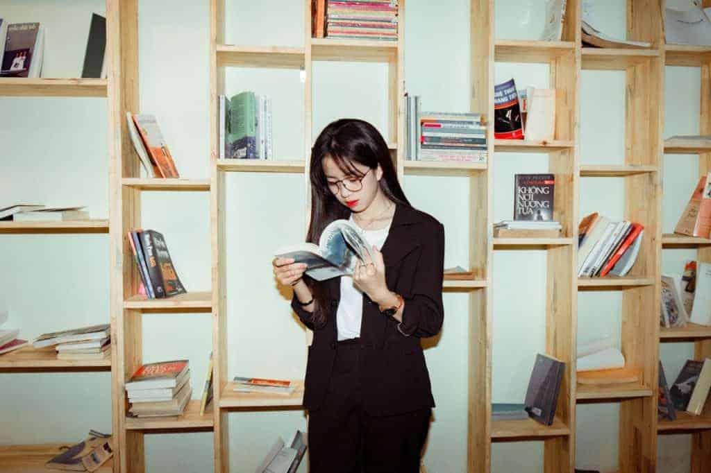 Imagem de uma estudante lendo um livro de administração.