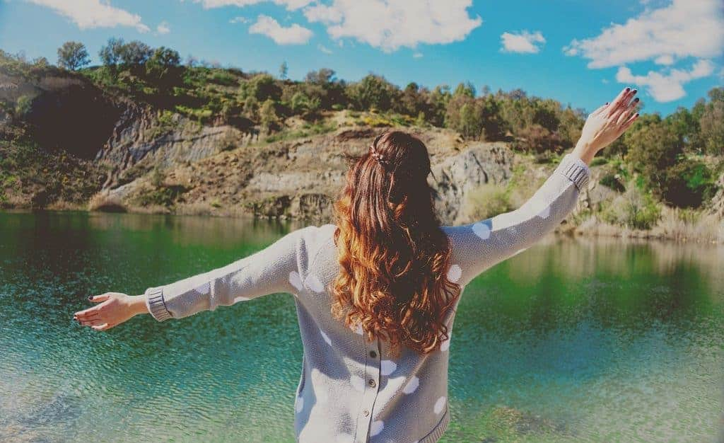 Mulher de costas olhando para o lago.