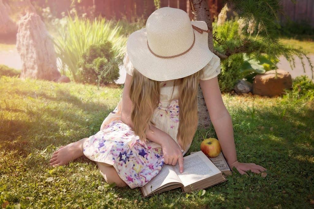 Na foto uma menina sentada em um jardim de chapéu e vestido lendo um livro.