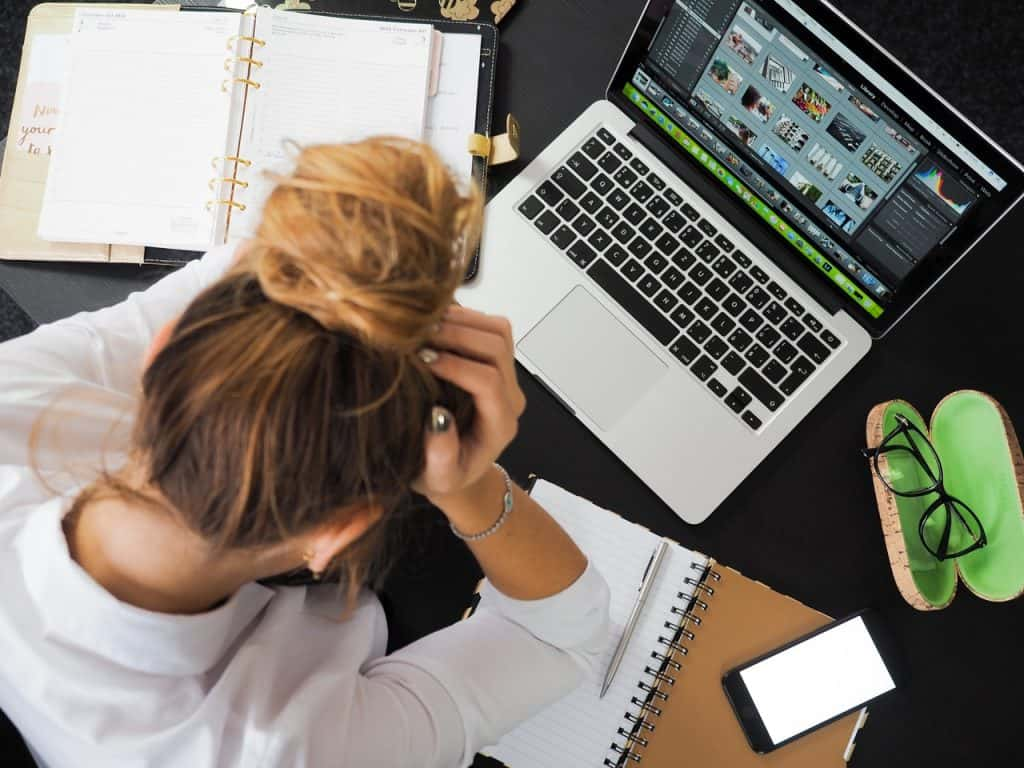 Moça com as mãos no cabelo em situação estressante em frente ao computador.