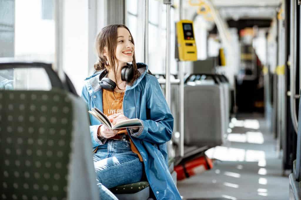 Na foto uma mulher dentro de um transporte público com um livro nas mãos olhando para o lado sorrindo.