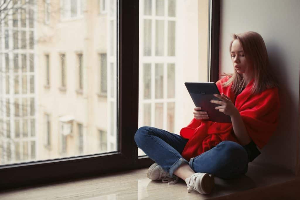 Na foto uma mulher sentada ao lado de uma janela lendo em um tablet.
