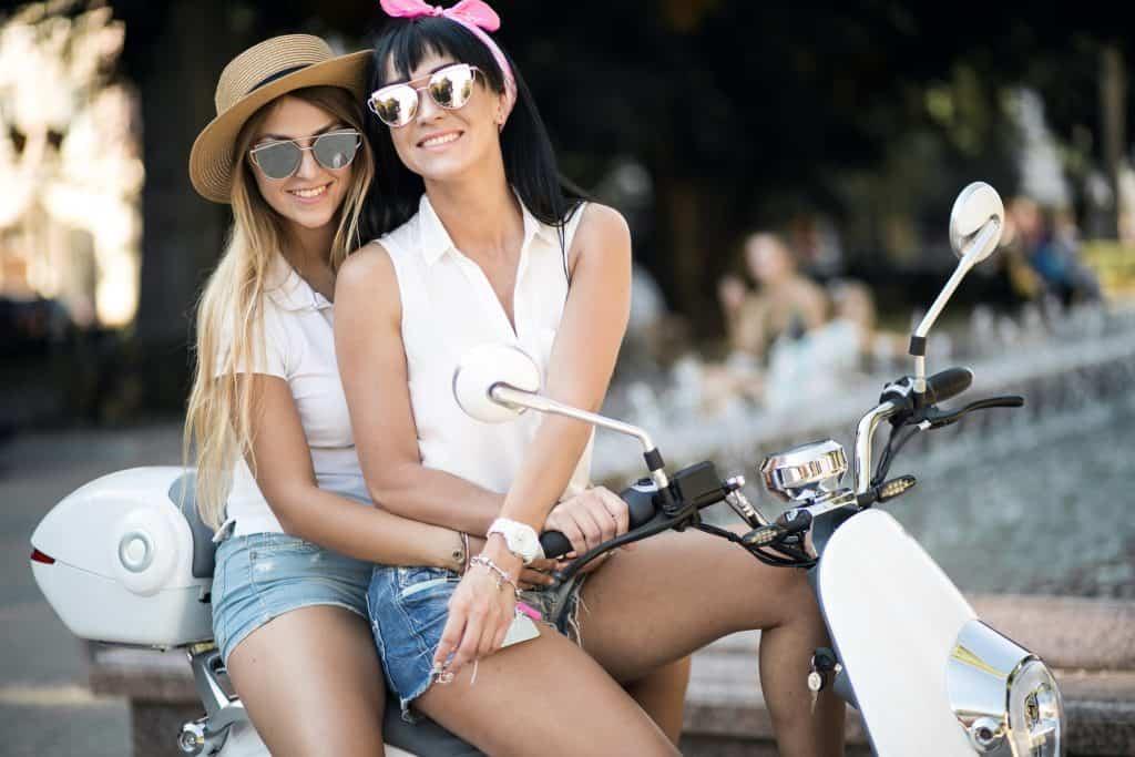 Duas jovens sentadas em scooter equipada com bauleto traseiro