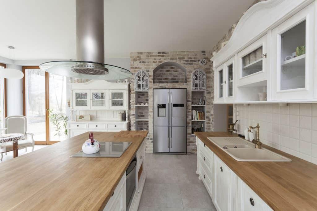 Na foto uma cozinha com bancada em madeira, uma coifa prata e um geladeira french door ao fundo.