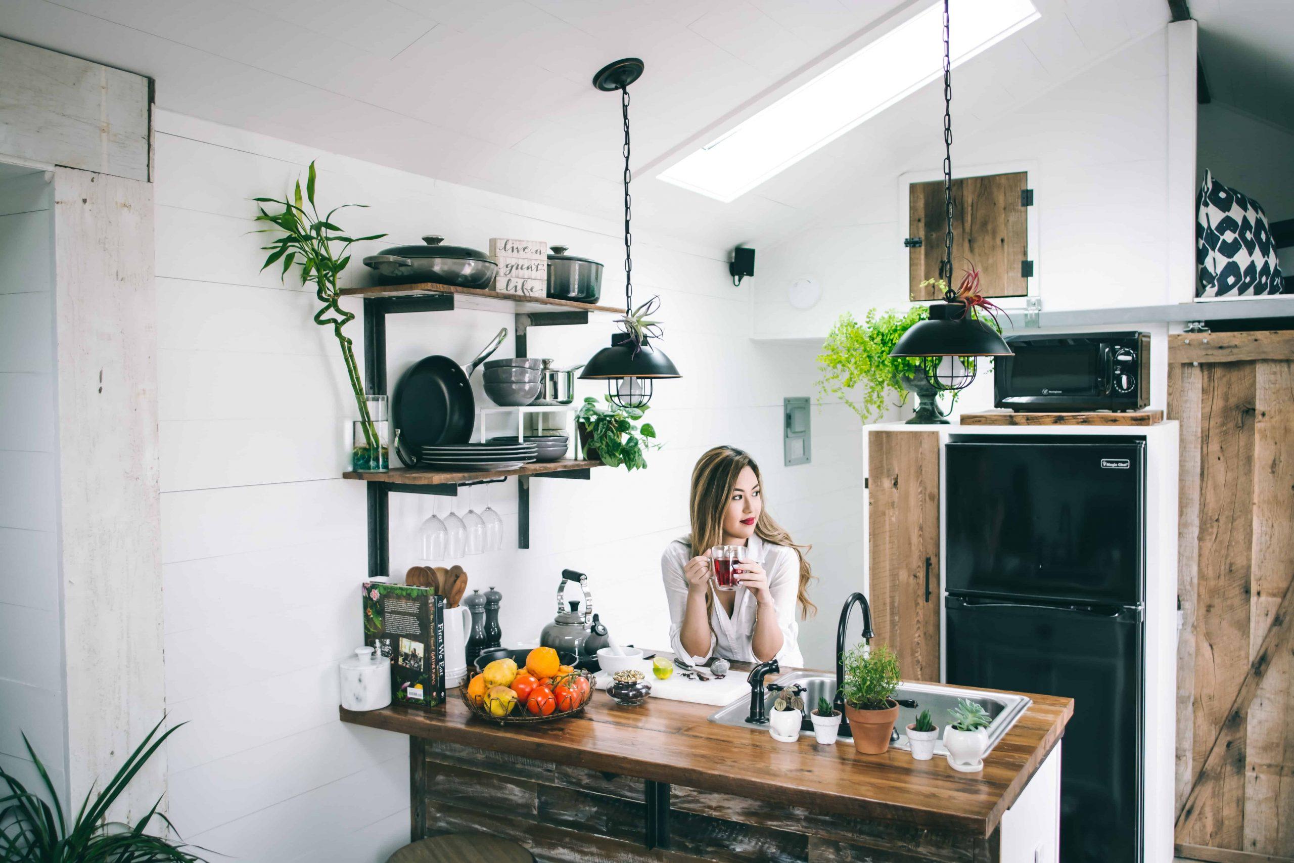 Na foto uma mulher tomando um chá em uma cozinha pequena com móveis de madeira.