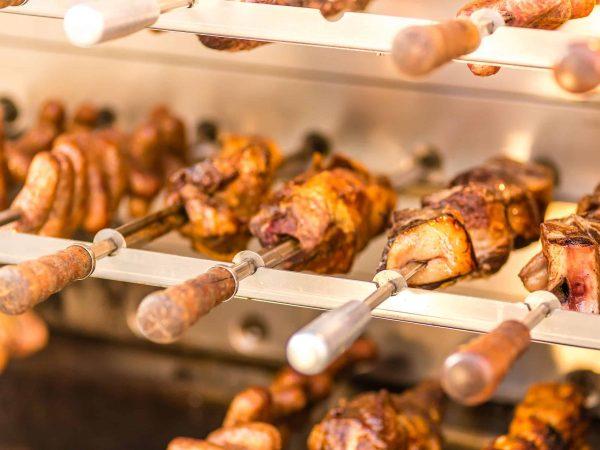 Imagem aproximada de grill giratório repleto de espetos com carne.