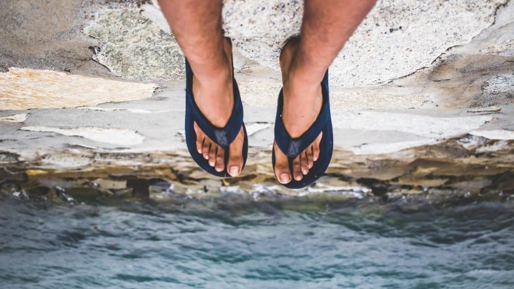 Pés com chinelos sobre o mar.