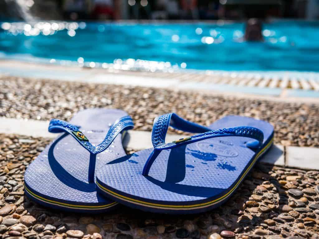 Imagem de havaianas azul na beira de piscina.