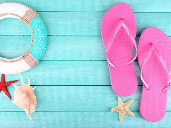 Bright flip-flops on color wooden background