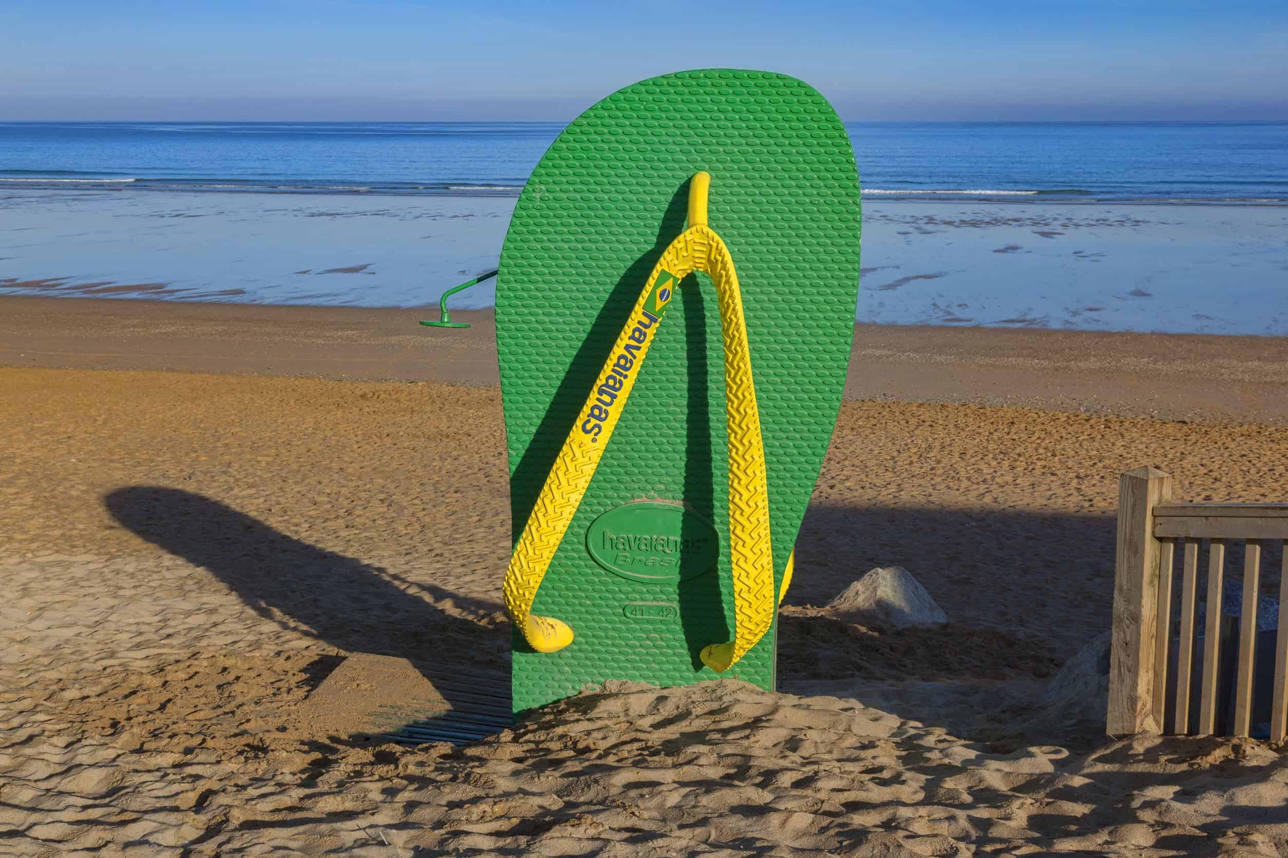 Imagem de havaianas masculina verde e amarela na beira do mar.