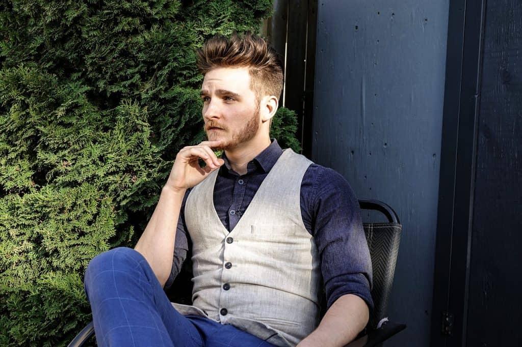 Homem sentado na cadeira com o cabelo arrumado com cera modeladora.