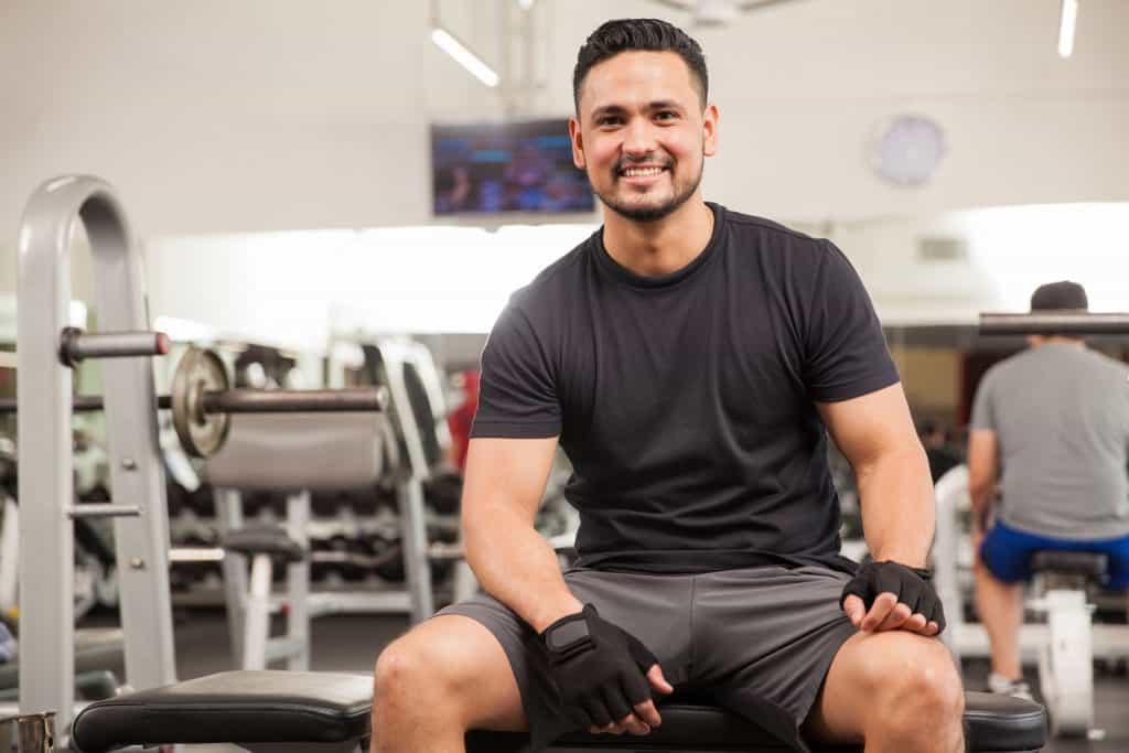 Imagem de homem sorrindo sentado em academia e usando luvas.
