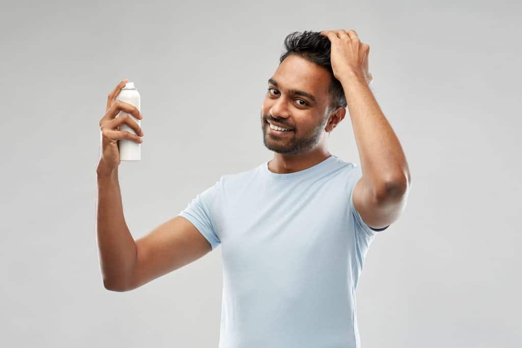 Foto de um homem passando shampoo seco no cabelo.