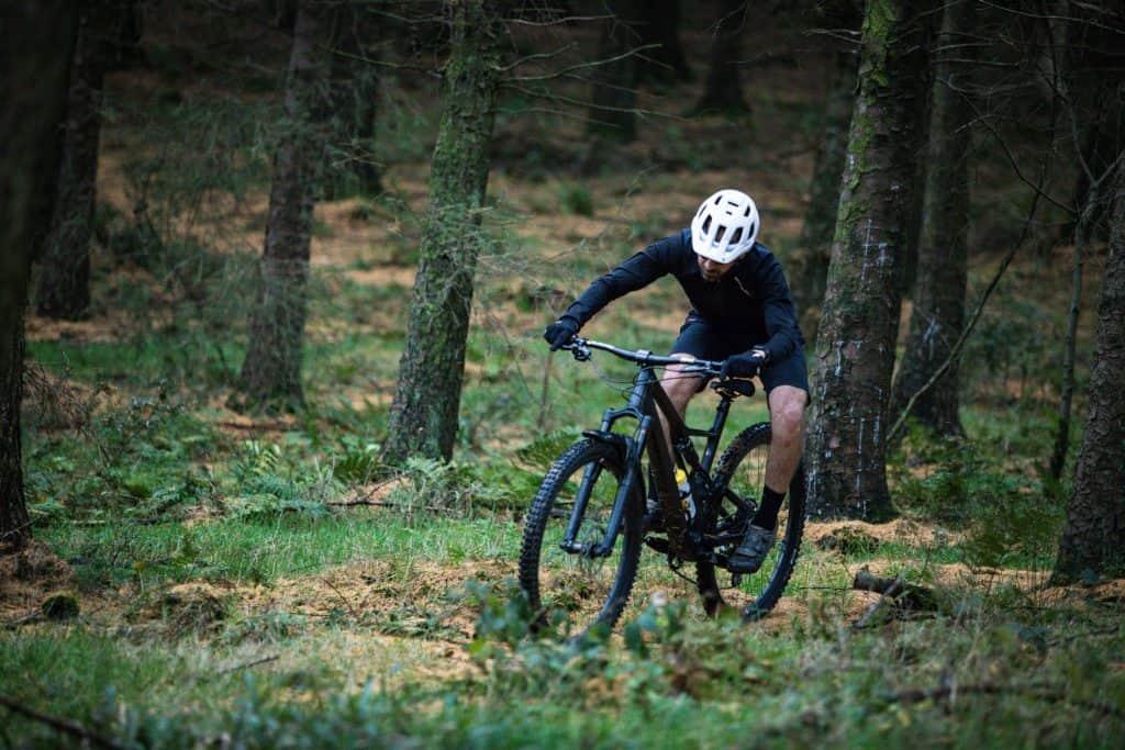 Imagem mostra um homem pedalando uma mountain bike numa floresta, com grama alta e muitos galhos espalhados no chão.