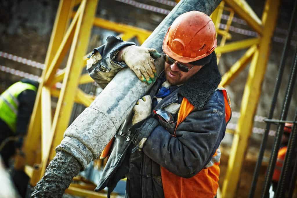 Homem com capacete com aba frontal trabalha em uma obra.