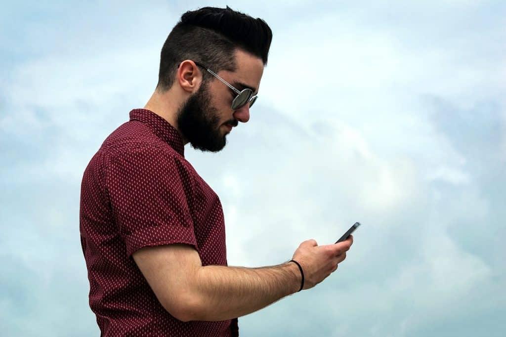 Homem teclando no smartphone.