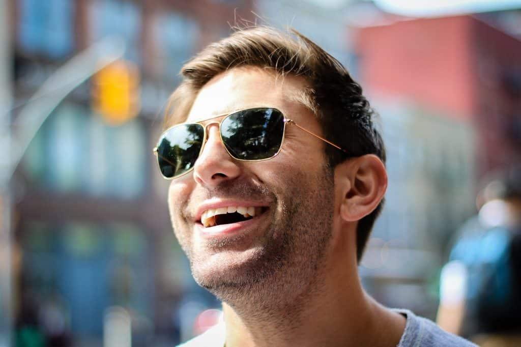 Imagem de homem sorrindo usando óculos de sol.