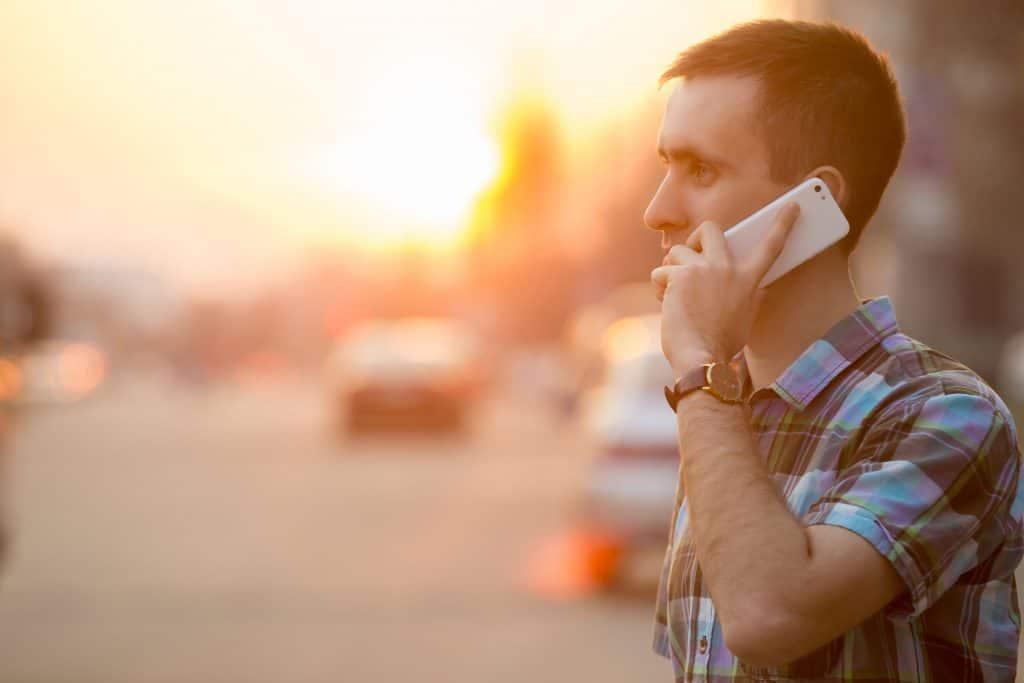 Na foto um homem falando no celular com um pôr do sol ao fundo.