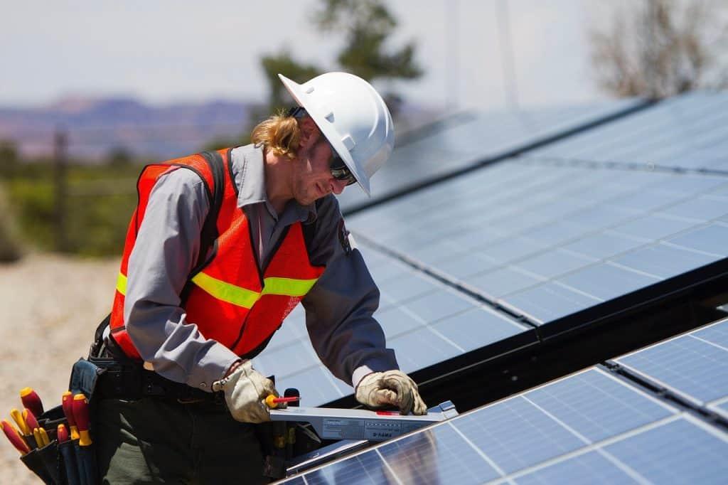 Fotografia de um profissional trabalhando ao lado de um painel solar, com equipamentos de segurança, realizando algum tipo de verificação.
