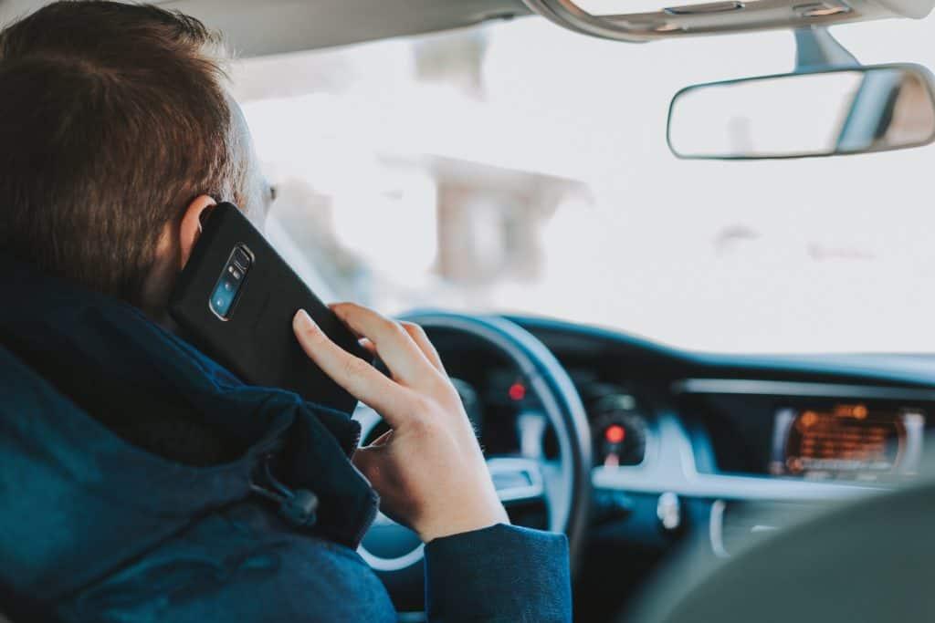 Imagem de um homem falando ao celular dentro do carro.