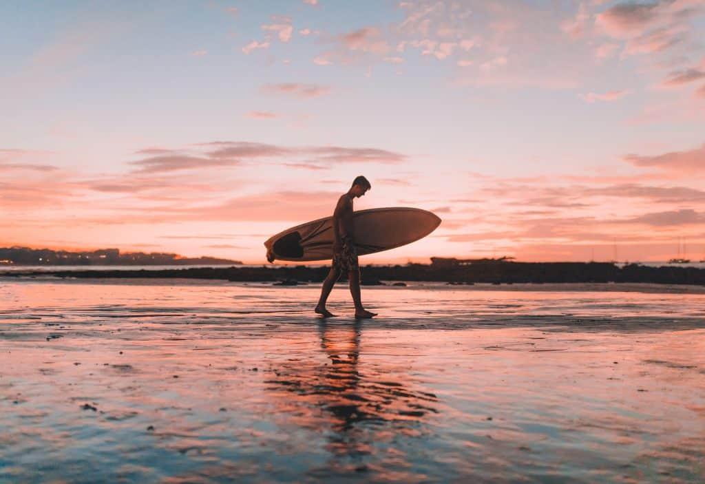 Imagem mostra um surfista sob uma luz crepuscular, caminhando na orla da praia com sua prancha debaixo do braço.