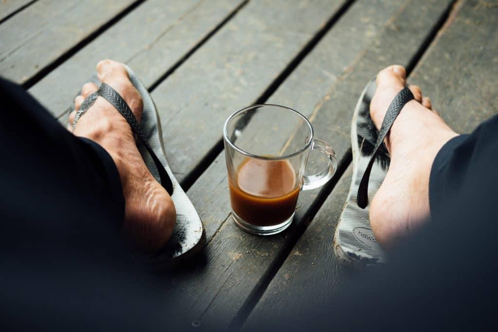 Pés de homem com Havaianas e xícara de café.