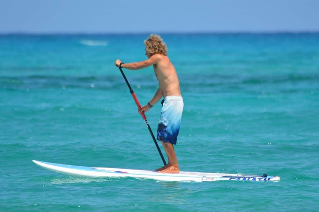 Imagem mostra um banhista remando sob um stand up paddle.