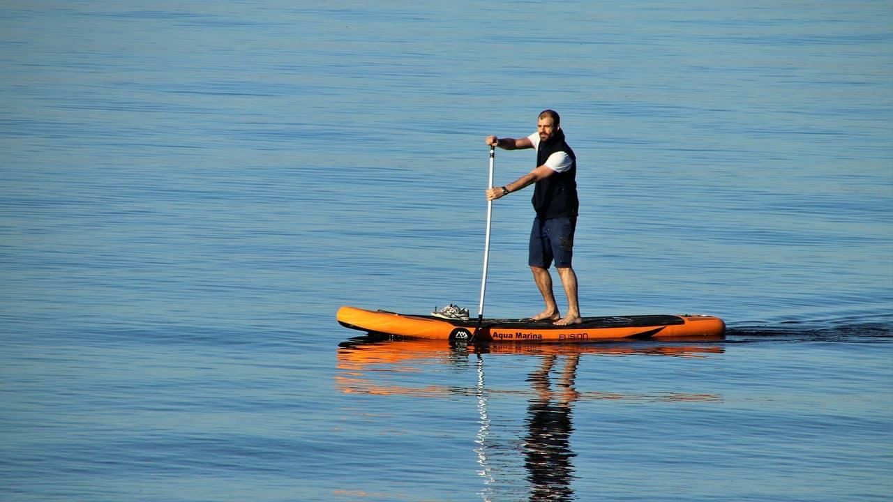Imagem mostra um homem remando sob um stand paddle inflável, que navega em águas calmas.