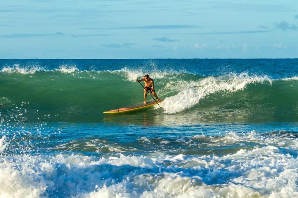 Imagem mostra um rapaz surfando numa onda com uma prancha de stand up.