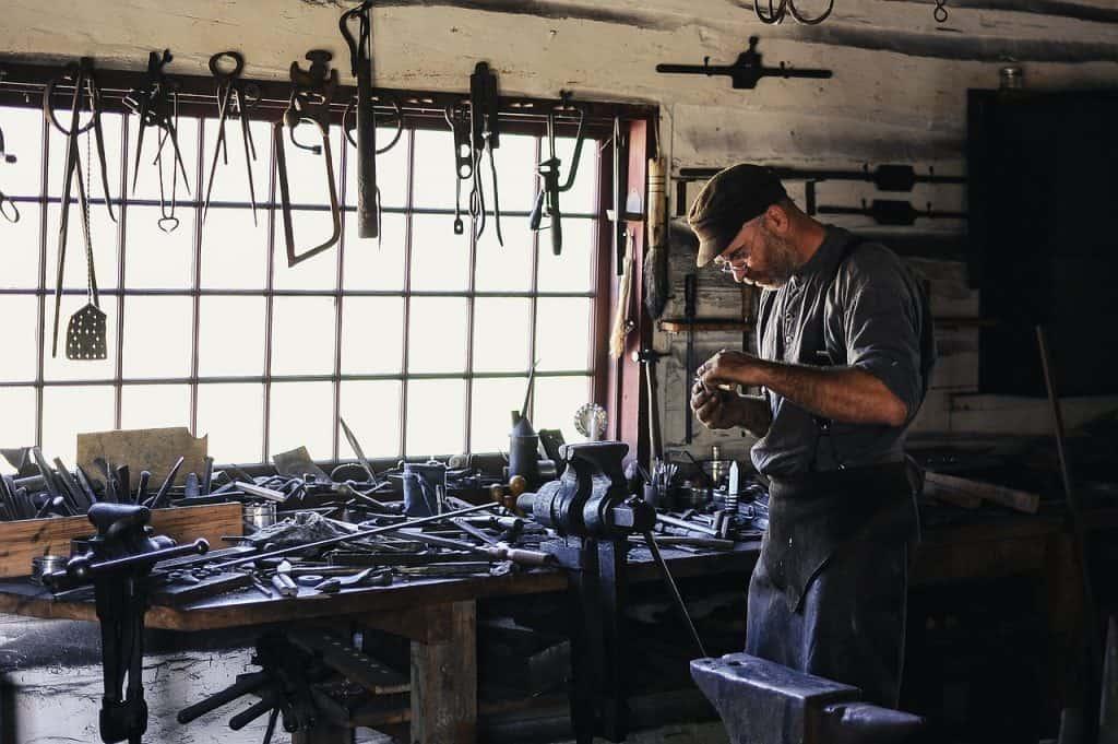 Homem utilizando ferramentas em uma oficina.