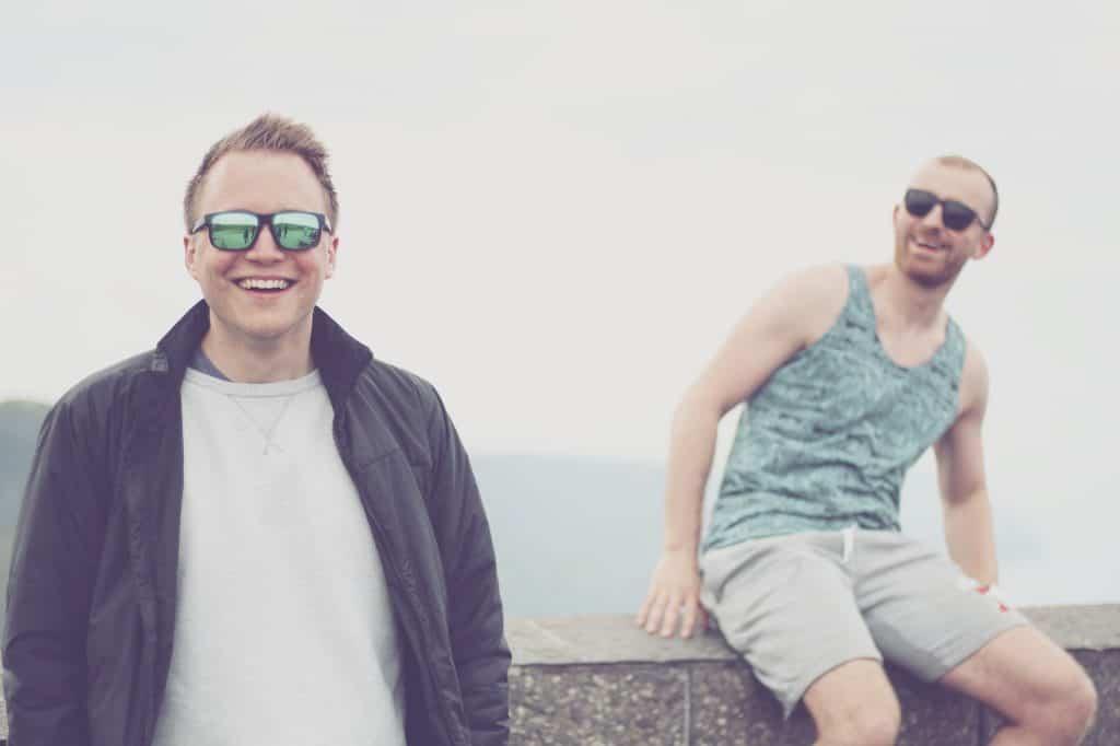 Imagem mostra dois homens, um sentado e um em pé, sorrindo e usando óculos de sol.