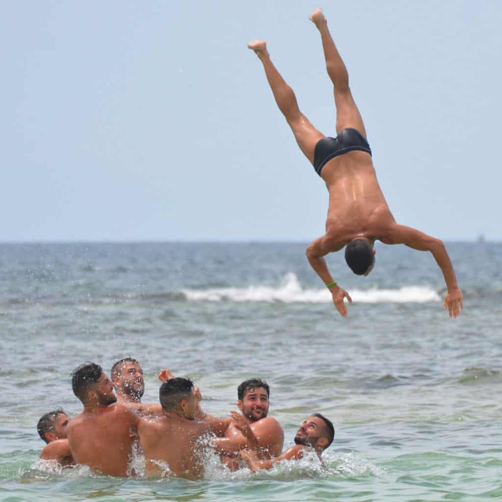 Imagem mostra um homem de sunga mergulhando enquanto outros se divertem no mar.